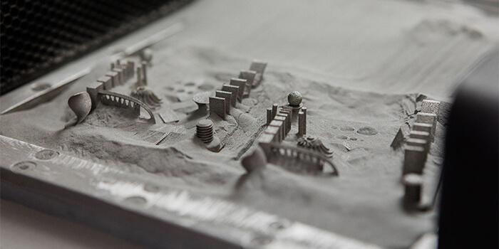 Pezzi sul piano di lavoro della stampante 3D a polvere di metallo Xact Metal